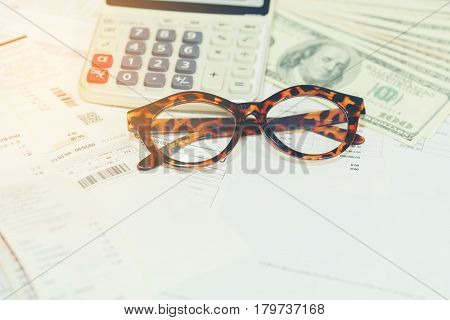 Business concept : Eyeglasses and household bills