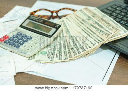 Finance concept : The United States hundred-dollar bills calculator bills eyeglasses and laptop on the table