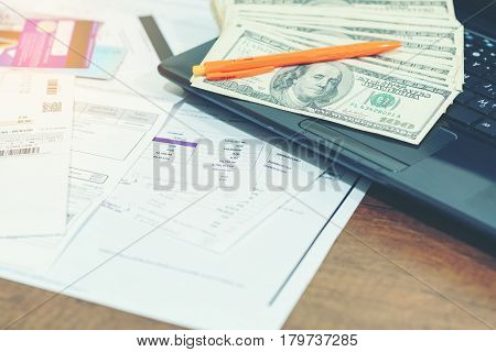 Finance concept : The United States hundred-dollar bills bills pen credit cards and laptop on the table
