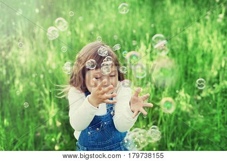 Сute little girl playing with soap bubbles on the green lawn outdoor. Happy childhood concept. Vintage style.