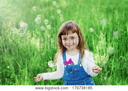 Сute little girl playing with soap bubbles on the green lawn outdoor. Happy childhood concept. Vintage toned.