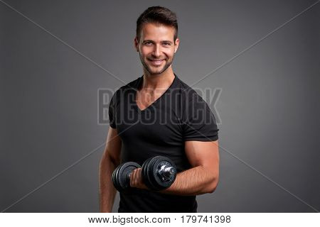 A handsome young man lifting weight and feeling confident