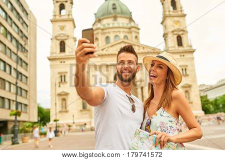 A beautiful young couple are taking a selfie with the St. Stephens Basilica behind them in Budapest, Hungary.
