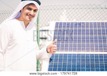 young arabian man standing in front of solar panel