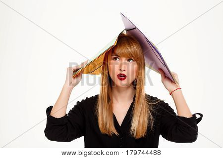 Young successful businesswoman holding folders above head, thinking over white background. Copy space.