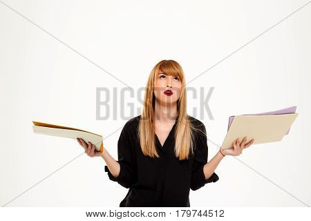 Tired young successful businesswoman holding folders, gesturing over white background. Copy space.