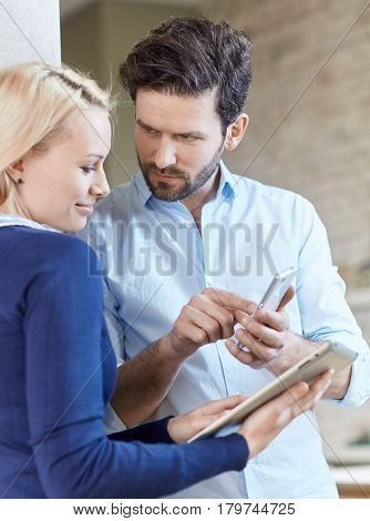 Young couple using mobilephone and tablet computer.
