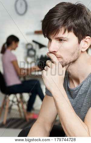 Portrait of thoughtful young man sitting hand on chin, thinking. Side view.