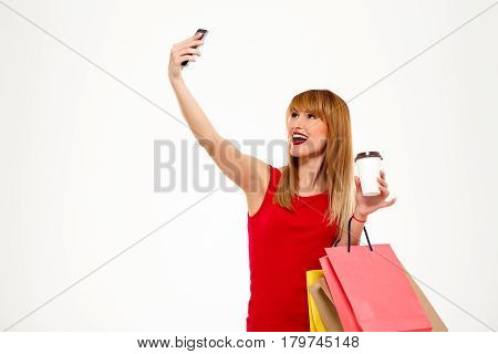 Young beautiful girl with purchases making selfie, smiling, holding coffee over white background. Copy space.