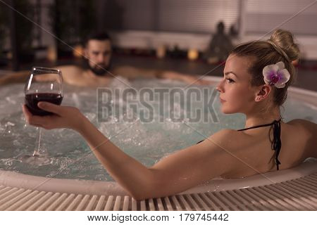 Couple in love enjoying the romantic atmosphere of a jacuzzi bath drinking wine and relaxing