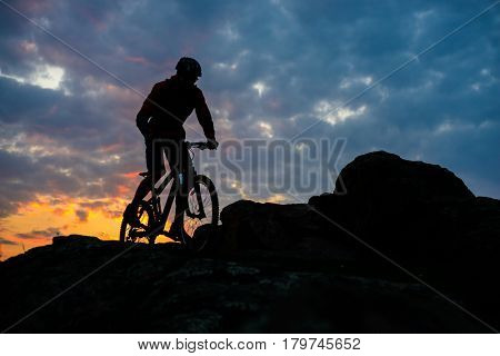 Silhouette of Cyclist Riding the Mountain Bike on the Spring Rocky Trail at Beautiful Sunset. Extreme Sports and Adventure Concept.