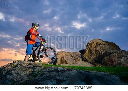 Cyclist Resting on the Mountain Bike on the Spring Rocky Trail at Beautiful Sunset. Extreme Sports and Adventure Concept.