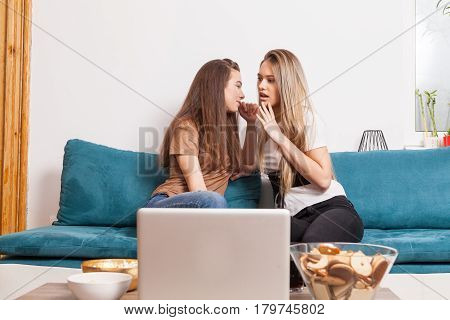 Friend is telling a secret to another on the sofa in the living room. Gossiping and secrets