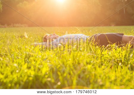 A handsome young man relaxing in the sunset and lying in the grass.