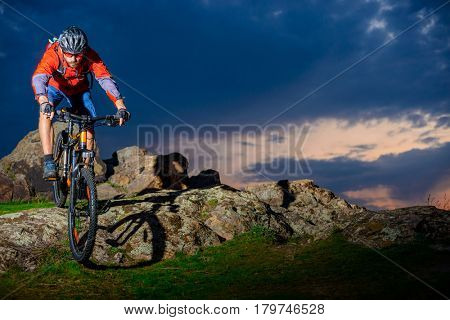Cyclist Riding the Mountain Bike Down Spring Rocky Hill at Beautiful Sunset. Extreme Sports and Adventure Concept.