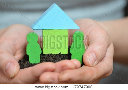 Female hands holding a piece of land with wooden house. Ecological home, family, construction and real estate concept