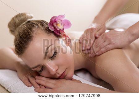 Woman lying in a beauty parlour enjoying relaxing back massage