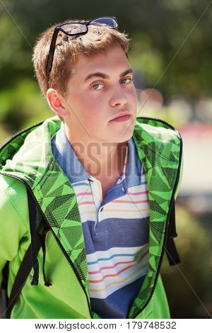 Happy teen boy in a hoodie walking on city street. Stylish fashion male model outdoor