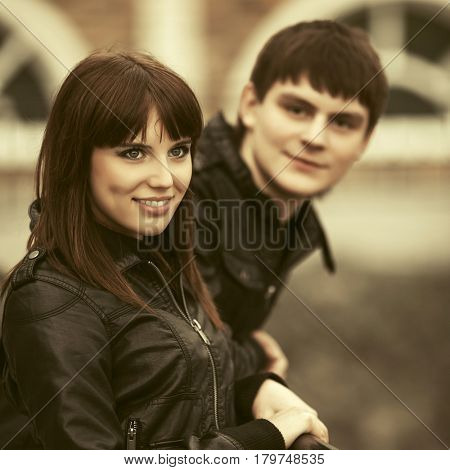 Happy young couple in love on city street. Stylish fashion model in leather jacket outdoor