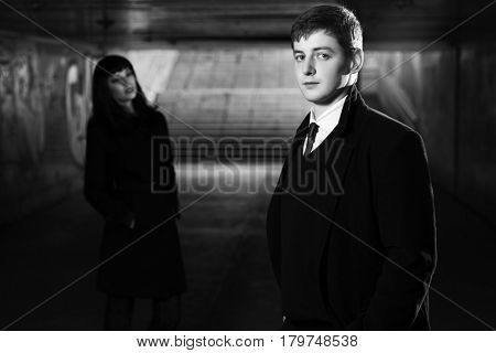 Young business couple in underground tunnel. Stylish fashion man and woman in black coat