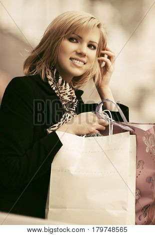 Happy young woman with shopping bags in the mall. Stylish fashion model in black coat