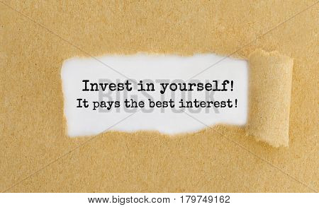 Invest In Yourself, It Pays The Best Interest Appearing Behind Ripped Brown Paper.