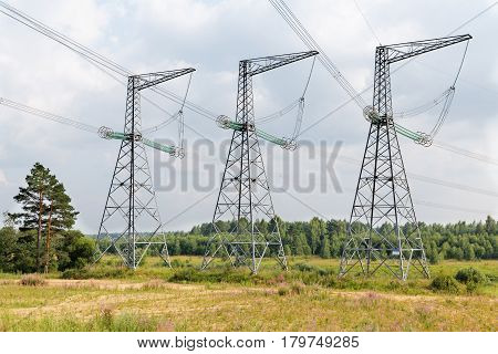 High-voltage transmission lines against the sky with clouds