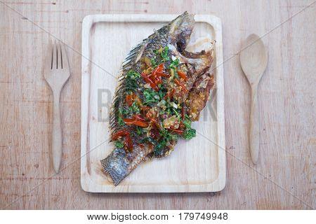 Thai style fish menu deep fried in chili sweet sauce on wood tray