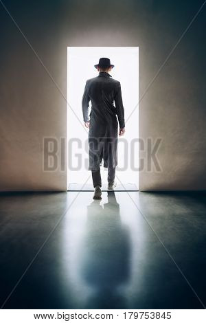 Man Silhouette Walking Away In The Light Of Opening Door In Dark Room