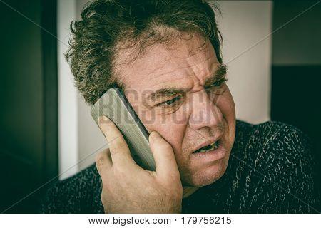 Bad news. Sad adult man talking on the phone