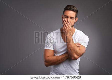 A worried handsome young man standing a white t-shirt