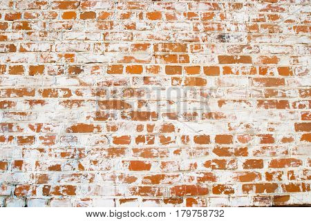 Old brick wall made of red brick. Partially the brick is painted white.