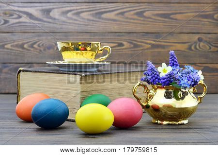 Easter eggs and cup of tea on wooden background
