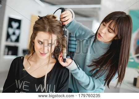 Kyiv, Ukraine - March 3, 2017: Closeup hairdresser coiffeur makes hairstyle. Female hairstyles on curling in a beauty salon.