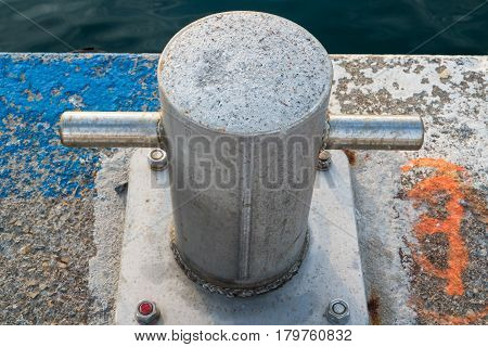 Closeup of a mooring bollard on a jetty by the sea