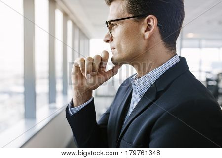 Side view shot of mature businessman standing beside office window looking outside and thinking with hand on chin.