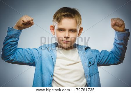 Closeup Portrait of Funny Little child. Sport Handsome Boy. Strong serious kid showing his hand biceps muscles.