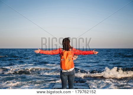 Young happy girl with orange backpack standing on a seaside breathing fresh air raising arms enjoying the view