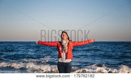 Young happy girl with backpack standing on a seaside breathing fresh air raising arms with eyes closed