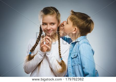 Teenage boy whispering in the ear of teen girl on a gray background. Positive human emotion, facial expression. Closeup. Communication concept.