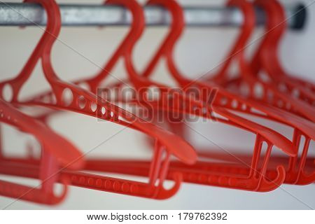 Red hangers without clothes hanging in a row in a closet