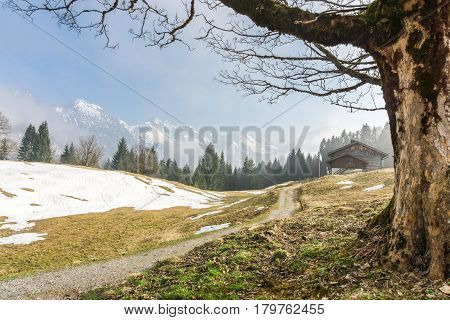 Hiking trail leads to a wooden mountain hut in the bavarian alps. Great view to snow-covered mountains with foggy clouds.
