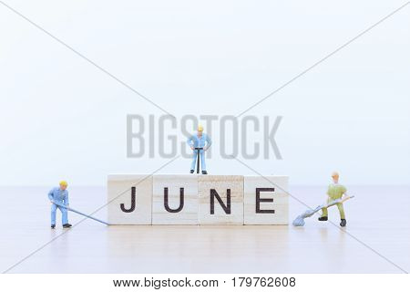June words with Miniature people worker on wooden floor