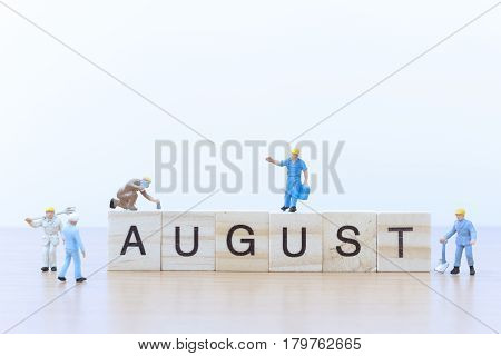 August words with Miniature people worker on wooden floor