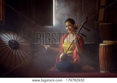 Beautiful women in traditional dress costume playing treble fiddle. Treble fiddle or soprano sounded string Thai music instrument Thai Cultural Arts Conservation Concept.