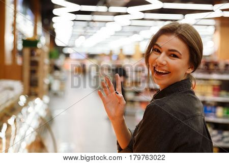 Image of young happy woman in supermarket choosing products and waving. Looking at camera.
