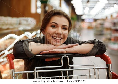 Image of young happy woman in supermarket lies on hands on shopping trolley. Looking at camera.