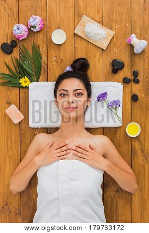 Relax at spa. Portrait of woman patient in ayurveda wellness center lies on wood with aroma spa accessories. Young beautiful indian girl with ideal clean skin rests with closed eyes in beauty parlor.