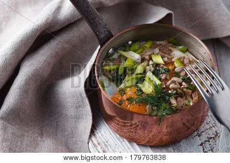 Scrambled eggs with greens in the copper pot on the white wooden table horizontal