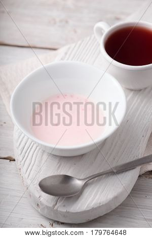 Fruit yogurt and cup of tea on the white wooden table